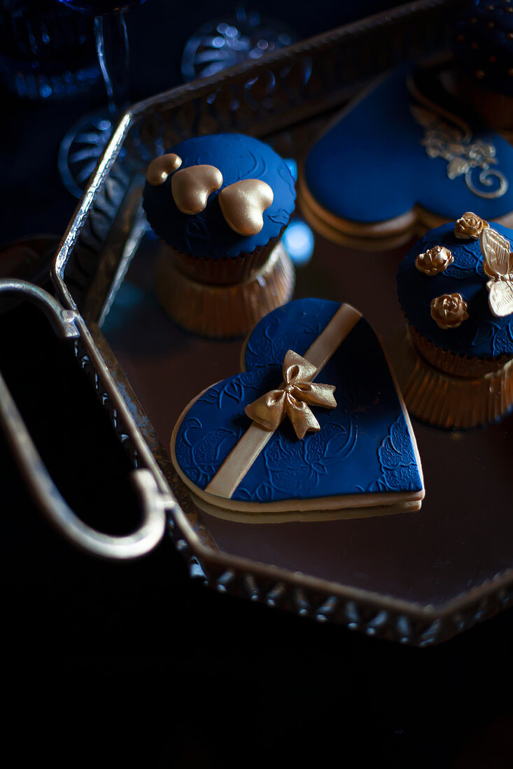 Cupcakes and biscuits with blue and gold toppings
