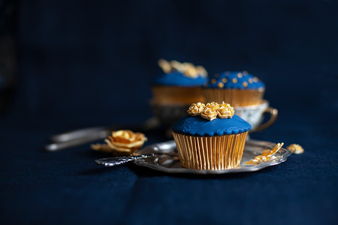 Perfectly decorated cupcakes with blue and gold toppings