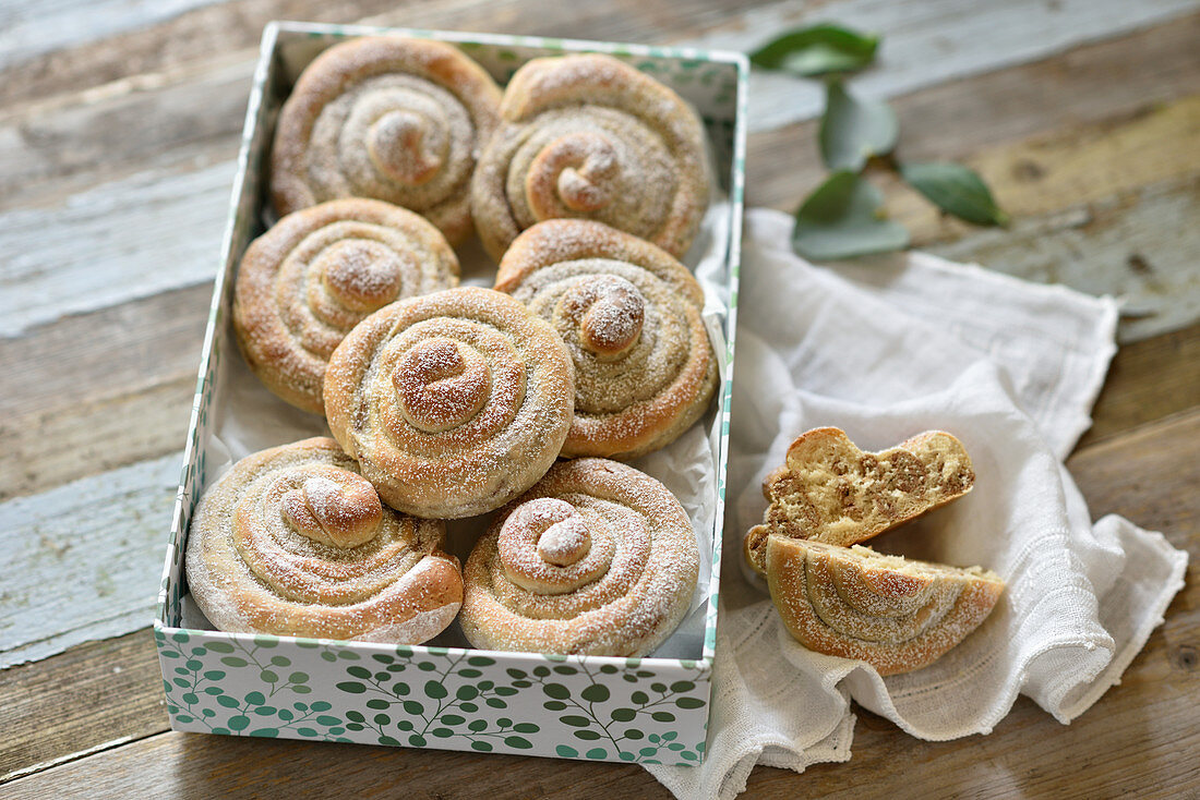 Vegan yeast dough buns with an almond filling and icing sugar in a gift box