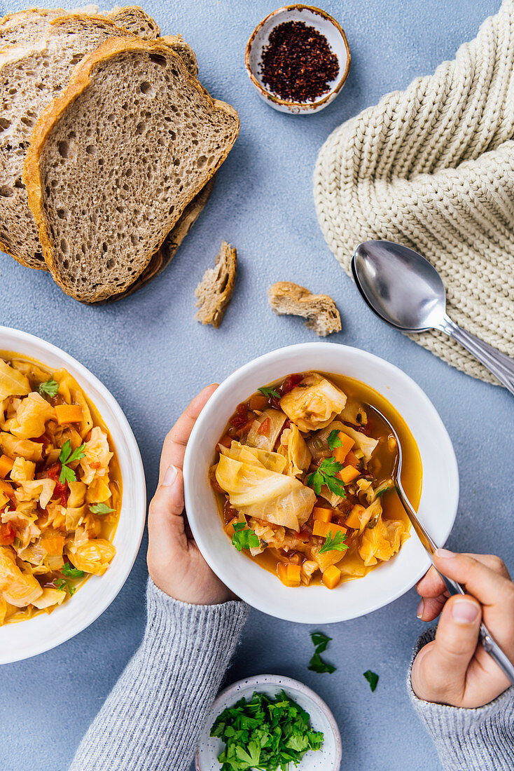 Woman having vegan cabbage soup in a white bowl, another bowl of soup, bread slices, chili flakes in a small ceramic bowl, parsley and spoons on the side photographed with a comforting winter feeling.