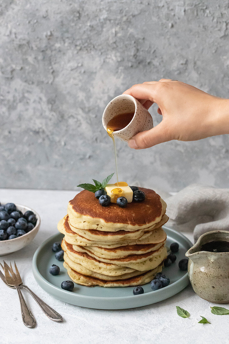 Pancakes with blueberries, butter, maple syrup and mint