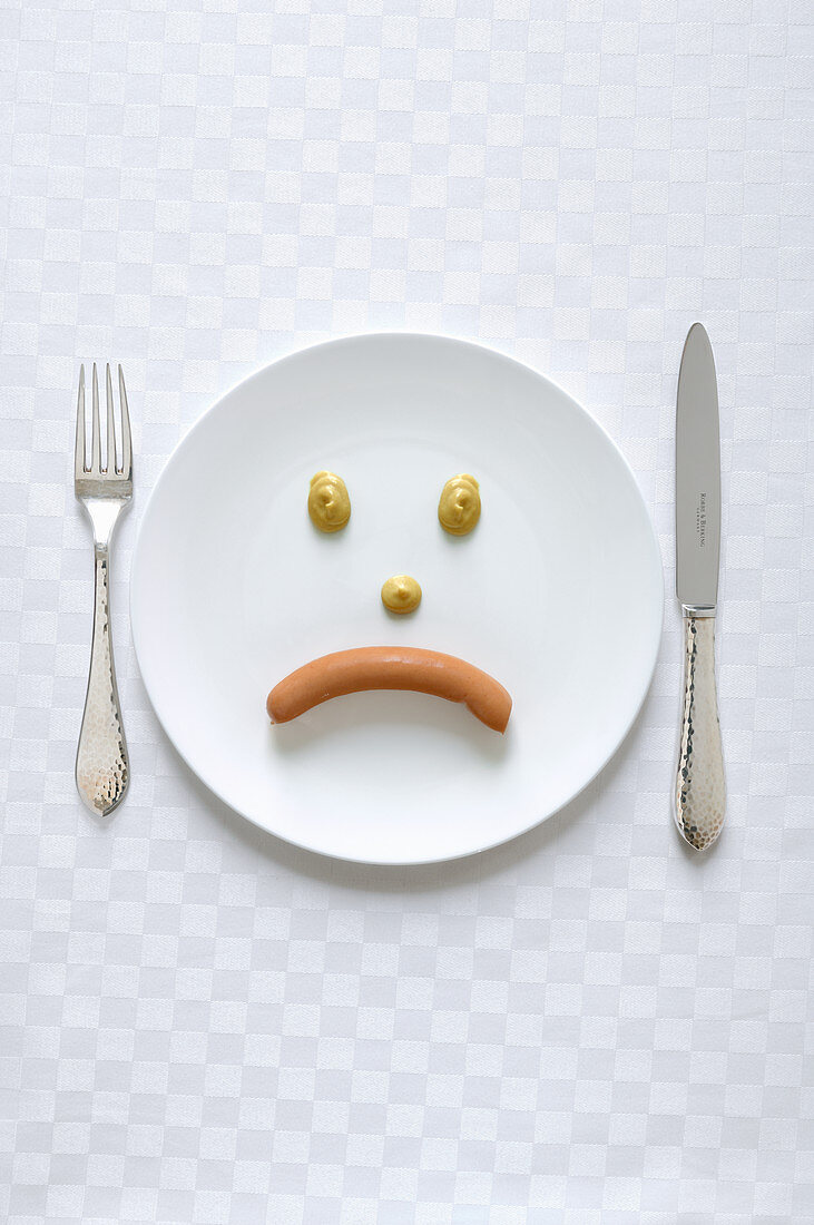 A sad face made from a sausage and mustard
