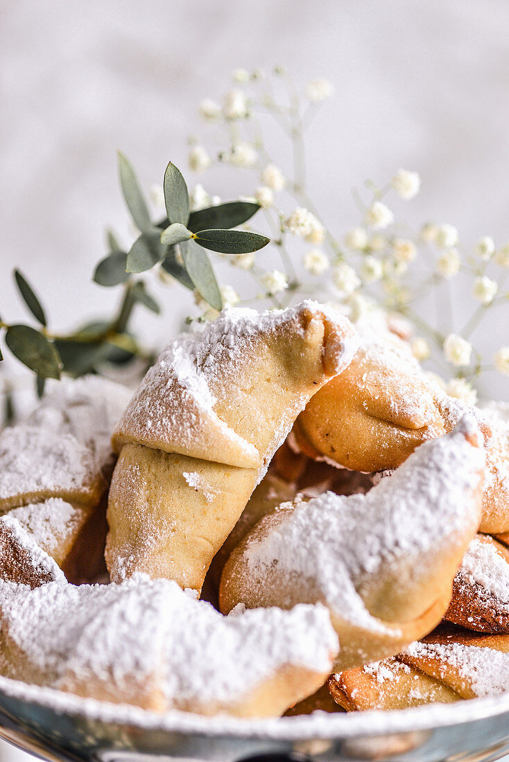 Brittle croissants on a plate sprinkled with powdered sugar