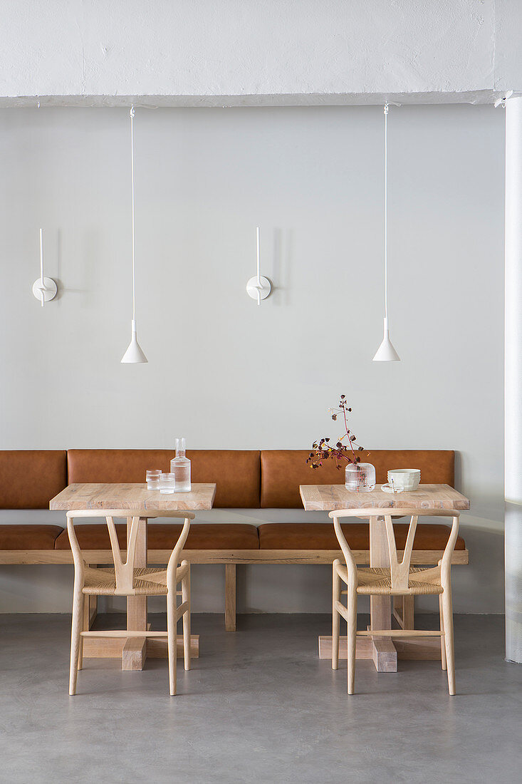 Designer chairs and small tables against leather bench in restaurant