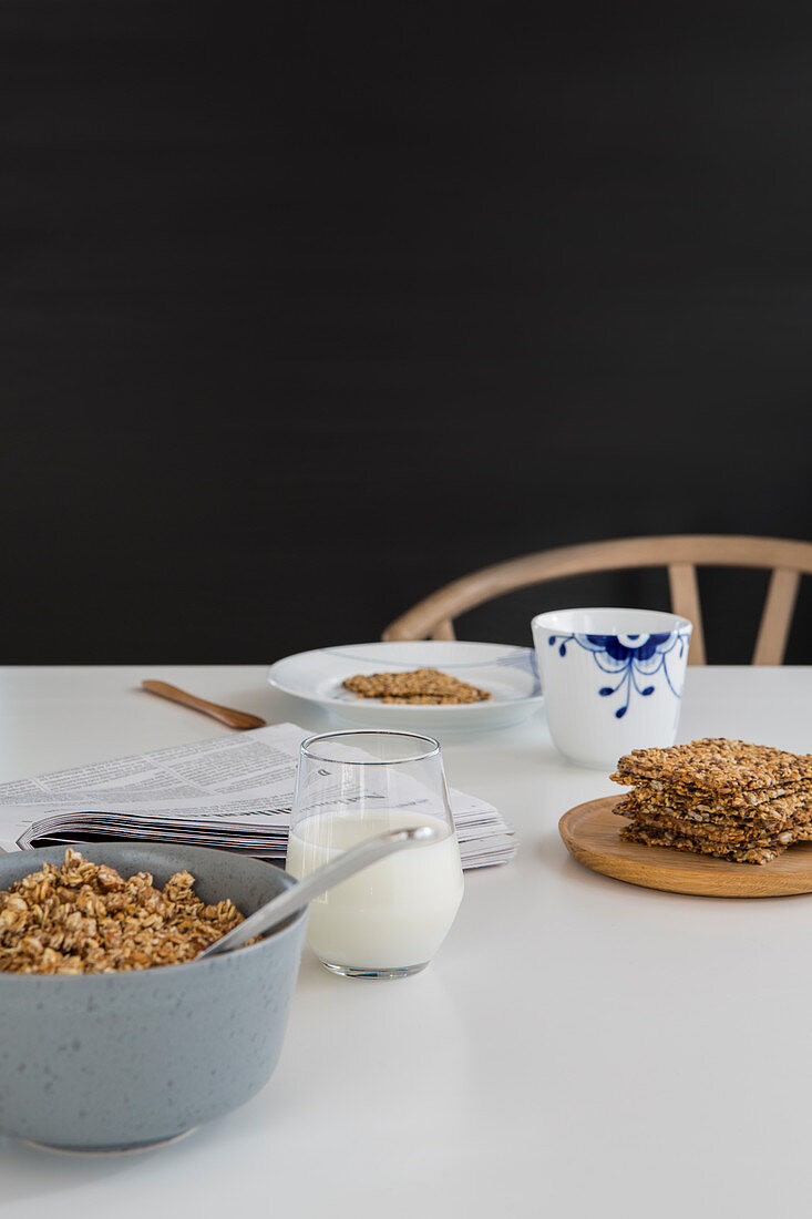 Simple, classic breakfast of muesli, milk and newspaper