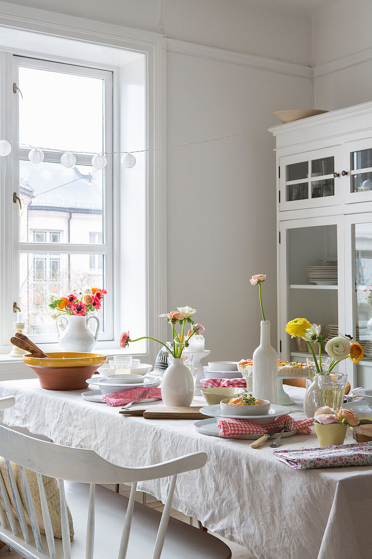 Flowers on summery set table in white dining room