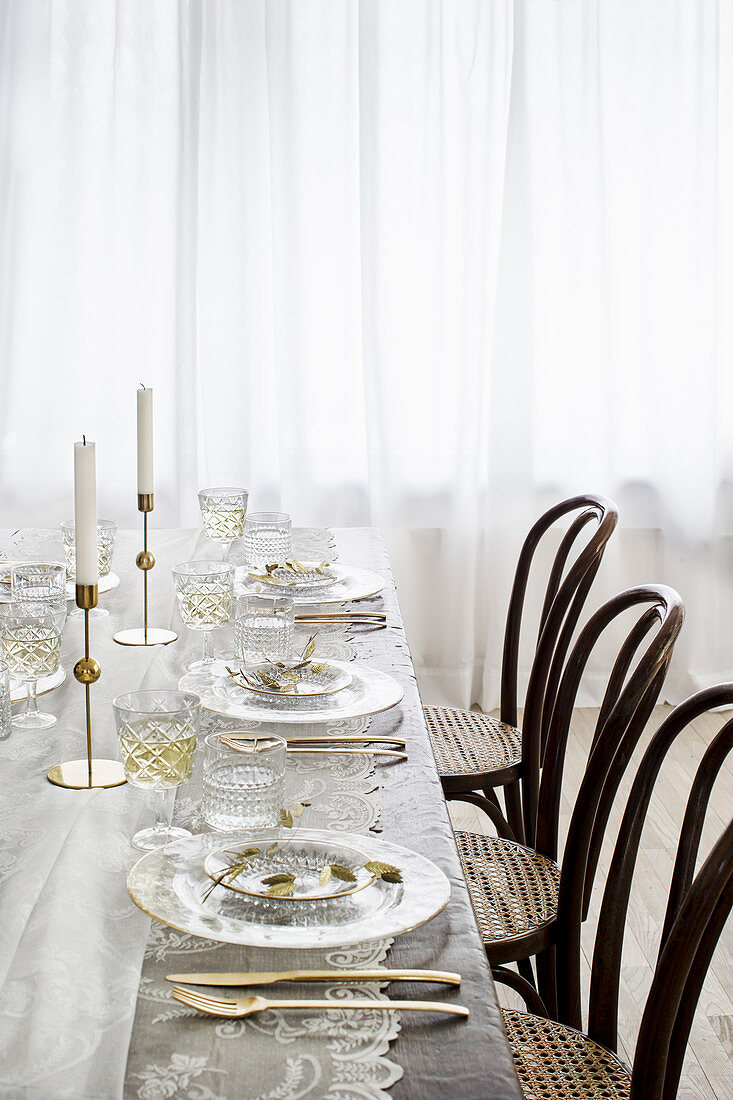 Bistro chairs around table set with lace tablecloth