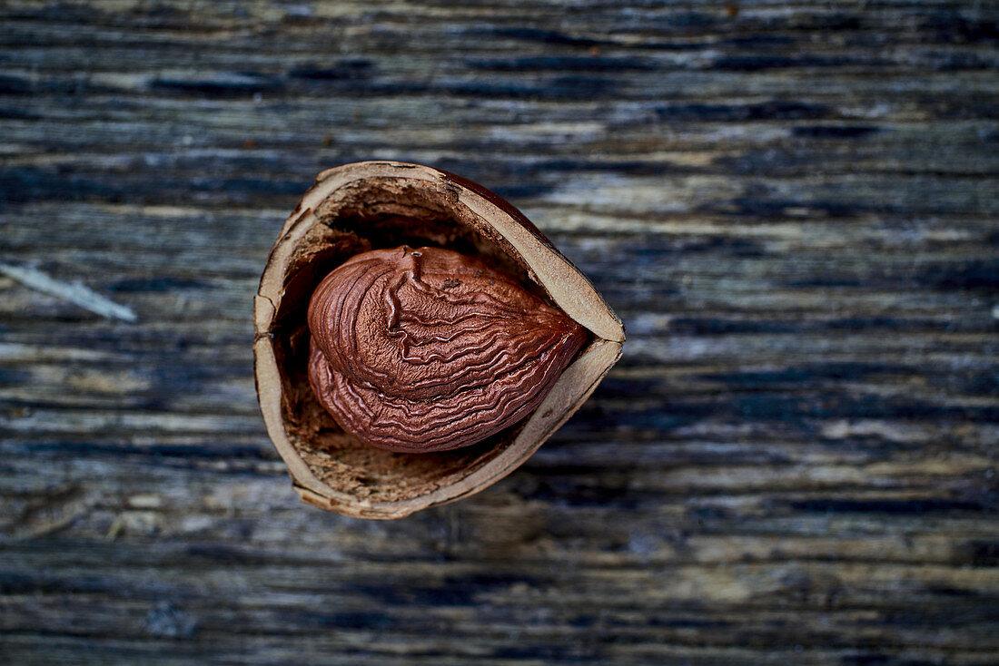 A half-shelled hazelnut on a wooden surface