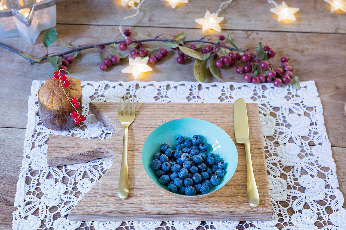 Bowl of blueberries and gold cutlery on lacy place mat