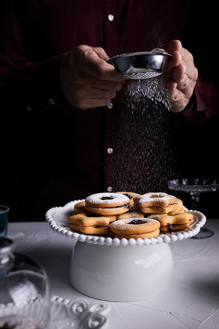 Dusting Linzer cookies with powder sugar