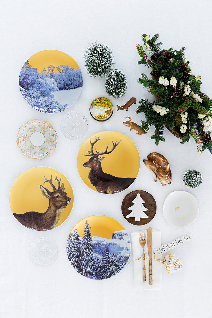 Christmas arrangement of china plates painted with deer and winter landscape motifs