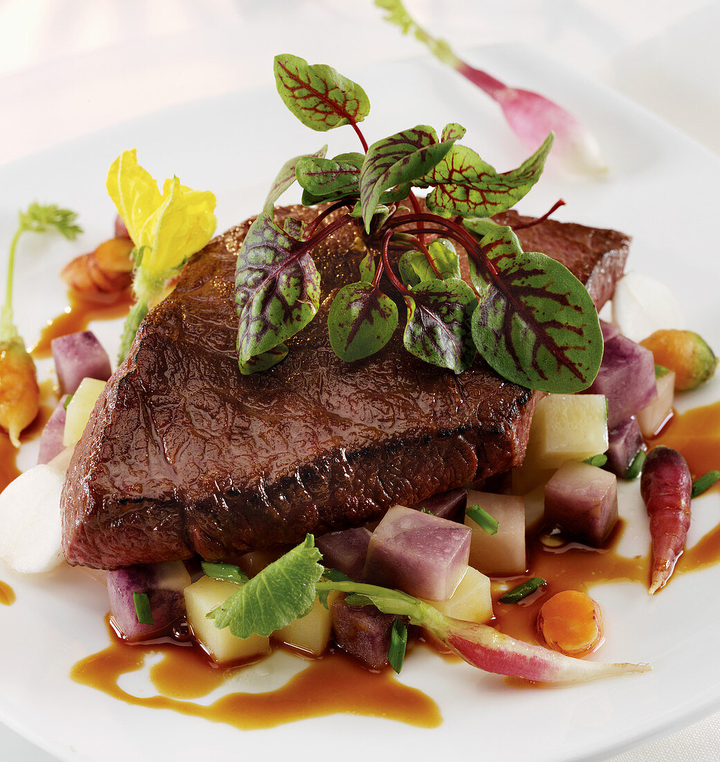 Broiled Flap Steak on a bed of root vegetables and demi glaze with red veined sorrel garnish