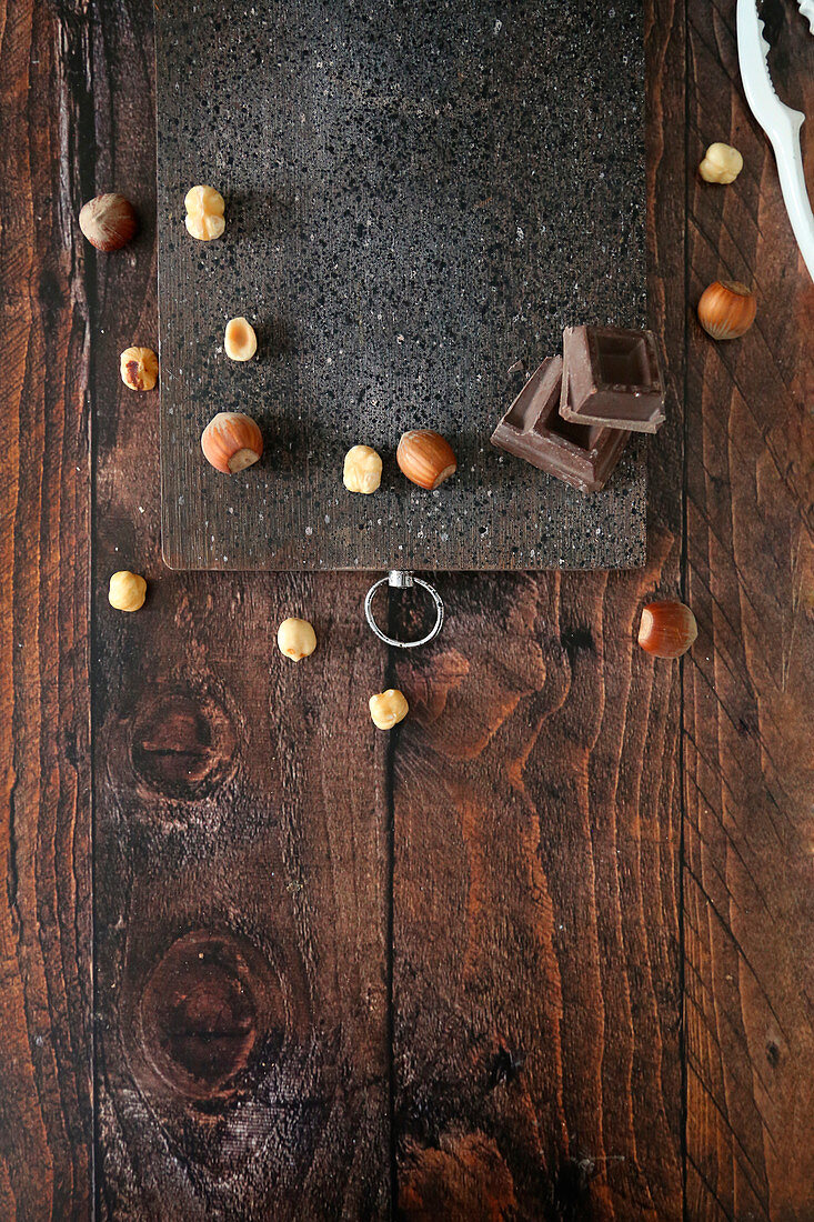 Wooden cutting board on table with hazelnuts and chocolate