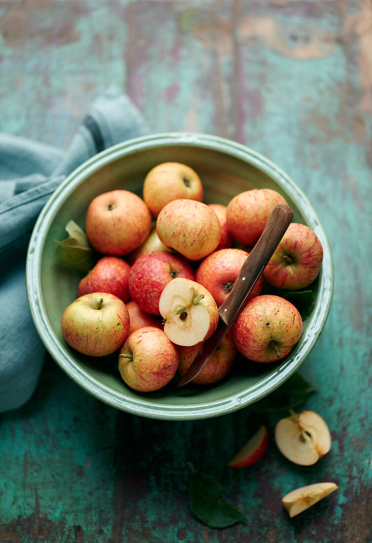 Small fresh apples with a peeling knife in a bowl