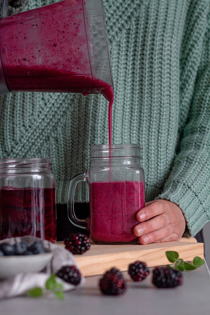 Berry smoothie filling from blender in glass