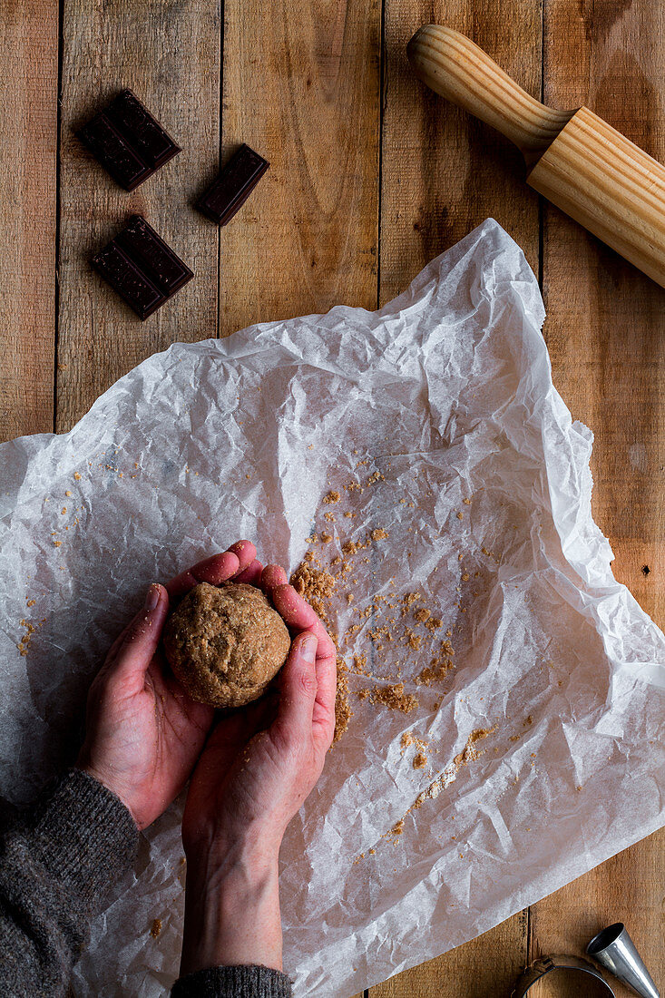 Hands holding chocolate dough above white baking paper chocolate metal cookie molds and rolling pin