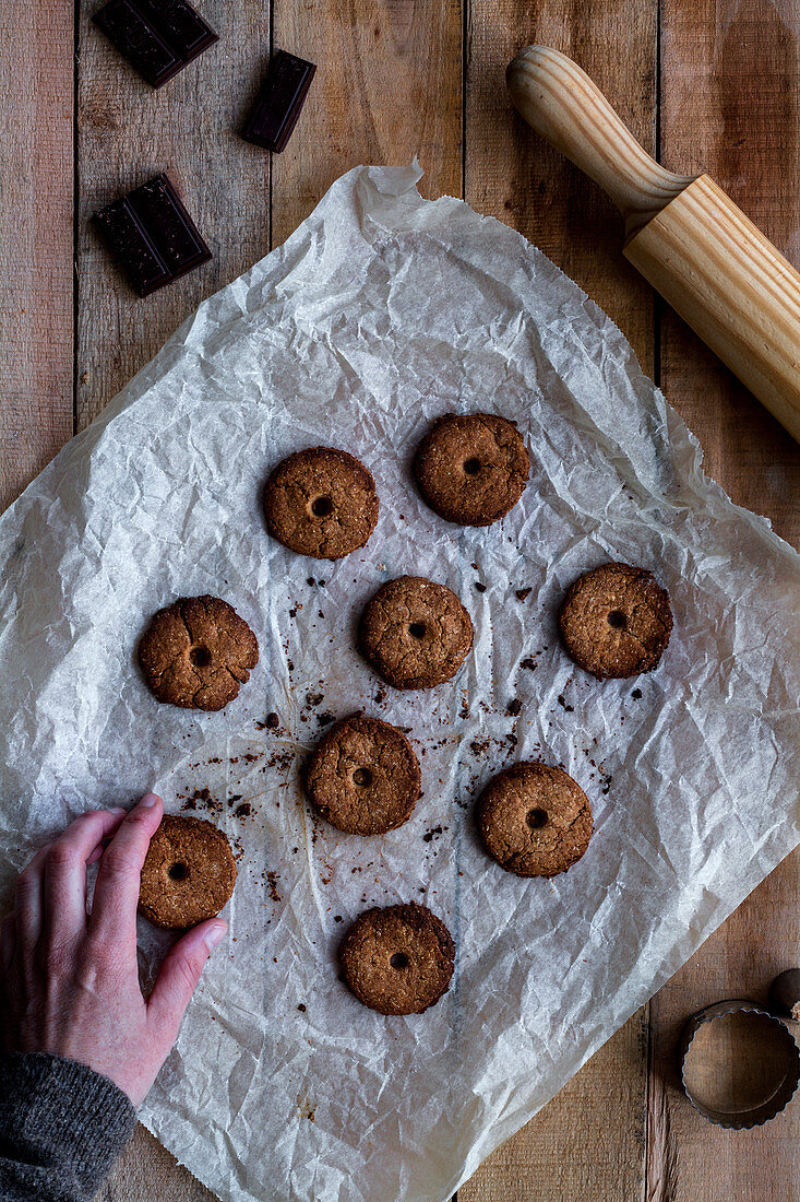 Hands holding chocolate baked cookies on white baking paper with chocolate