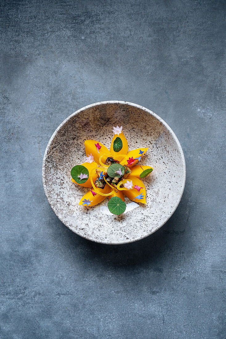 Fresh orange fruit and mushrooms decorated with small flowers and herbs