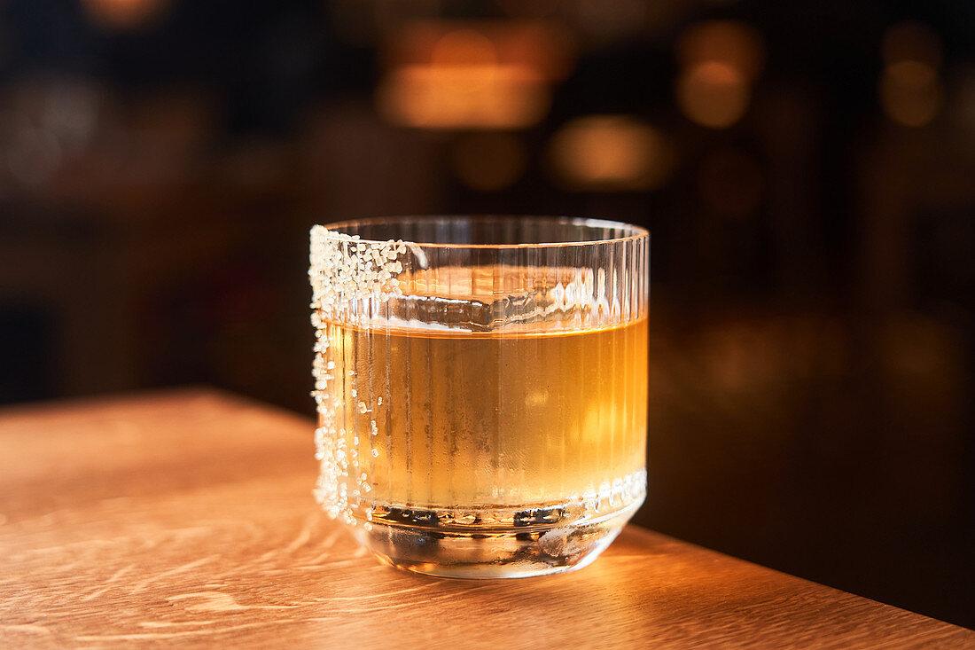 Amber Whisky Cocktail mit Eis und Zuckerverzierung