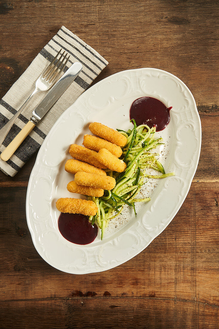 Fried cheese sticks with sliced cucumber and barbecue sauce on plate on wooden table