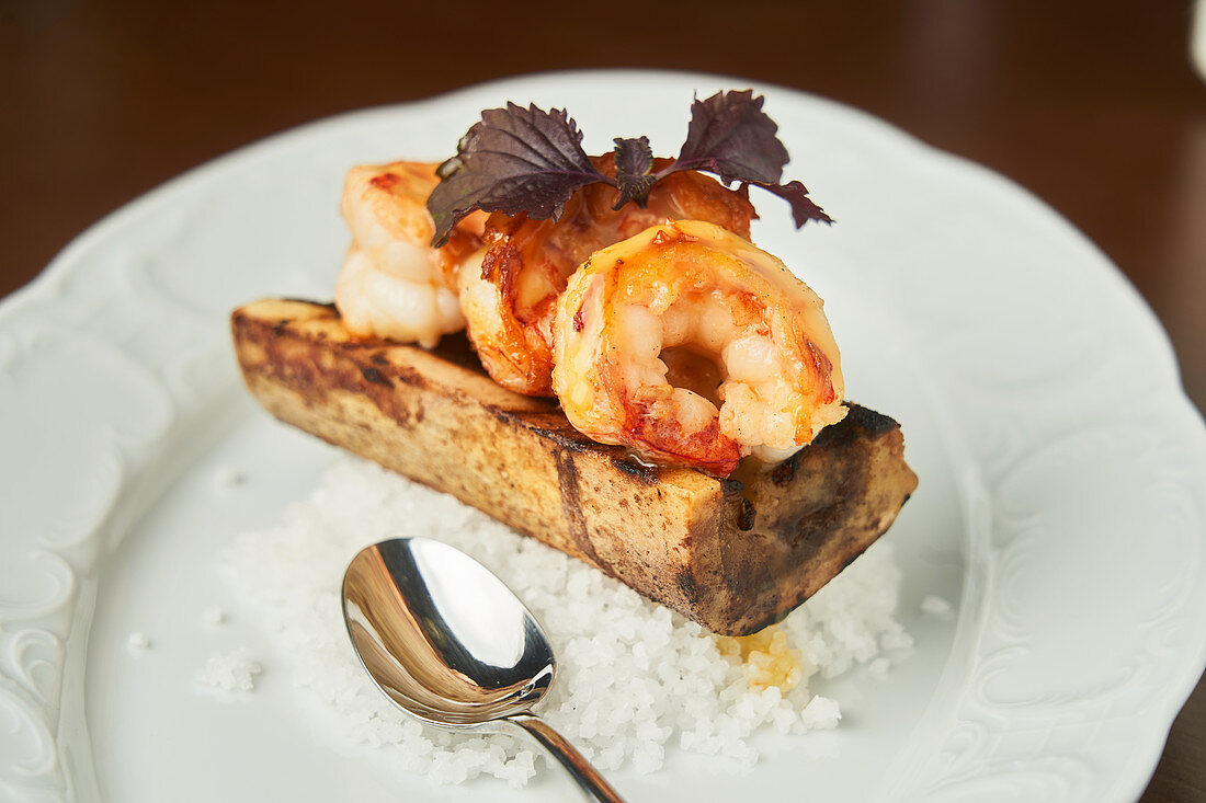 Grilled shrimps and white rice served on plate on table