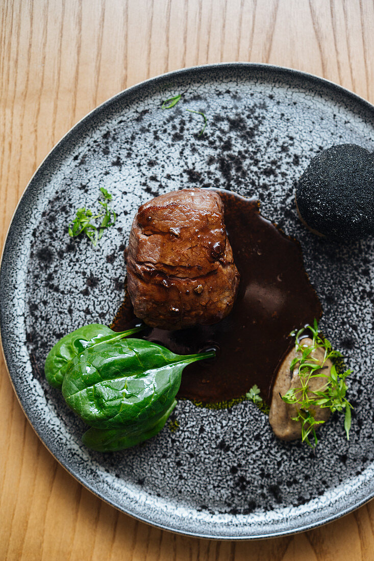 Meat steak with sauce and herbs served on metal silver plate on wooden background