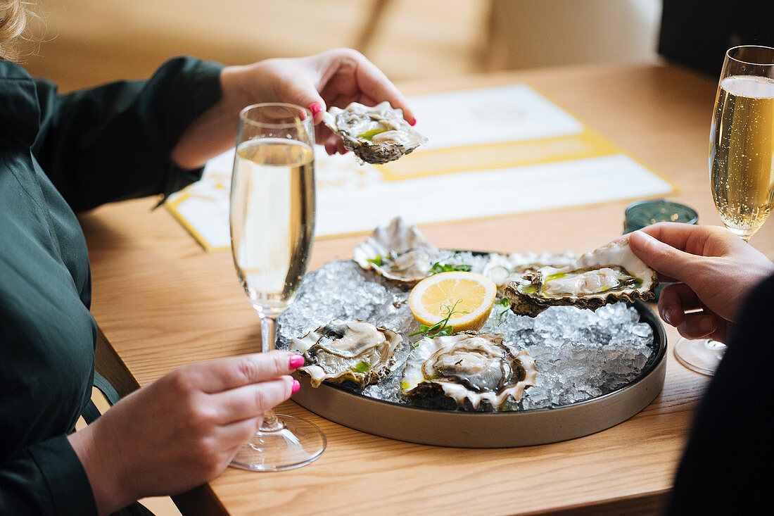 Couple with glasses of champagne trying delicious oysters with lemon and herbs