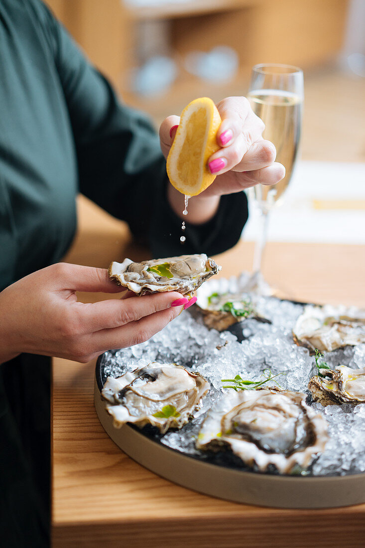 Person with glasses of champagne trying delicious oysters with lemon and herbs