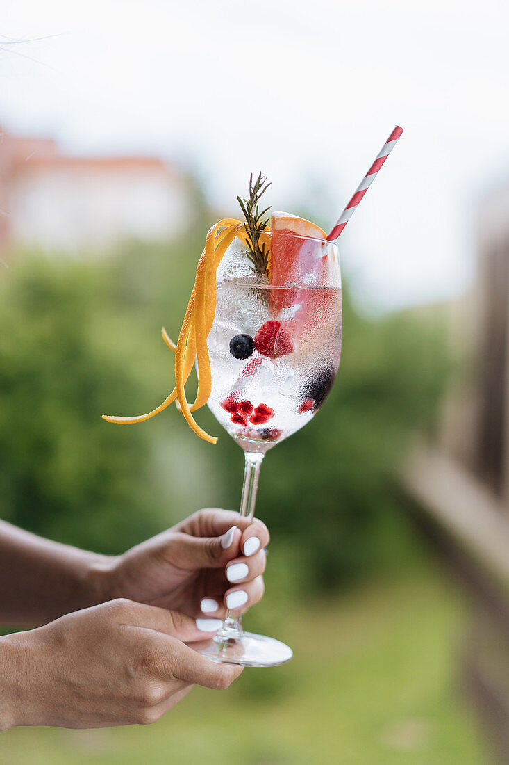 Female carrying cold drink with berries and grapefruit decorated with rosemary twig and orange peel