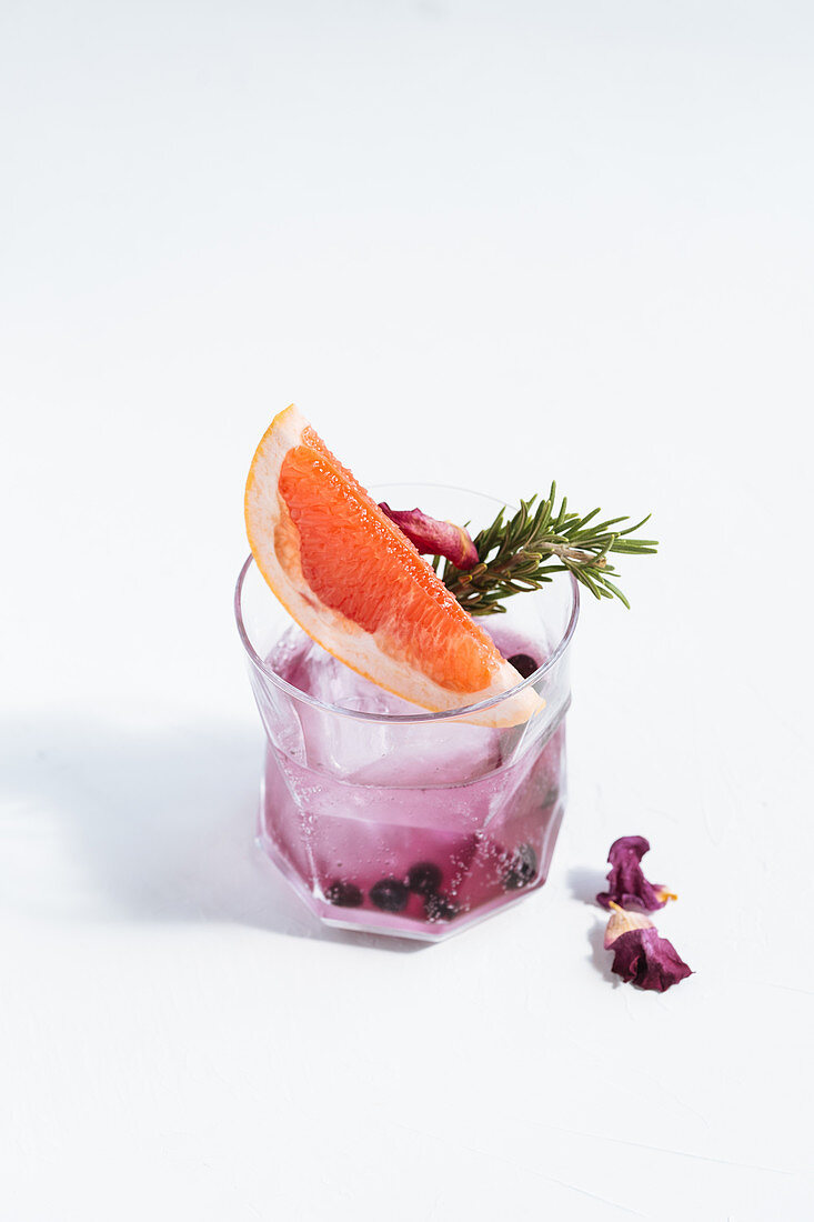 Glass with cocktail with slice of grapefruit, rosemary, dry blueberry, flowers and ice cube