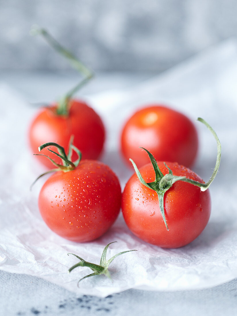 Fresh tomatoes with drops of water on paper