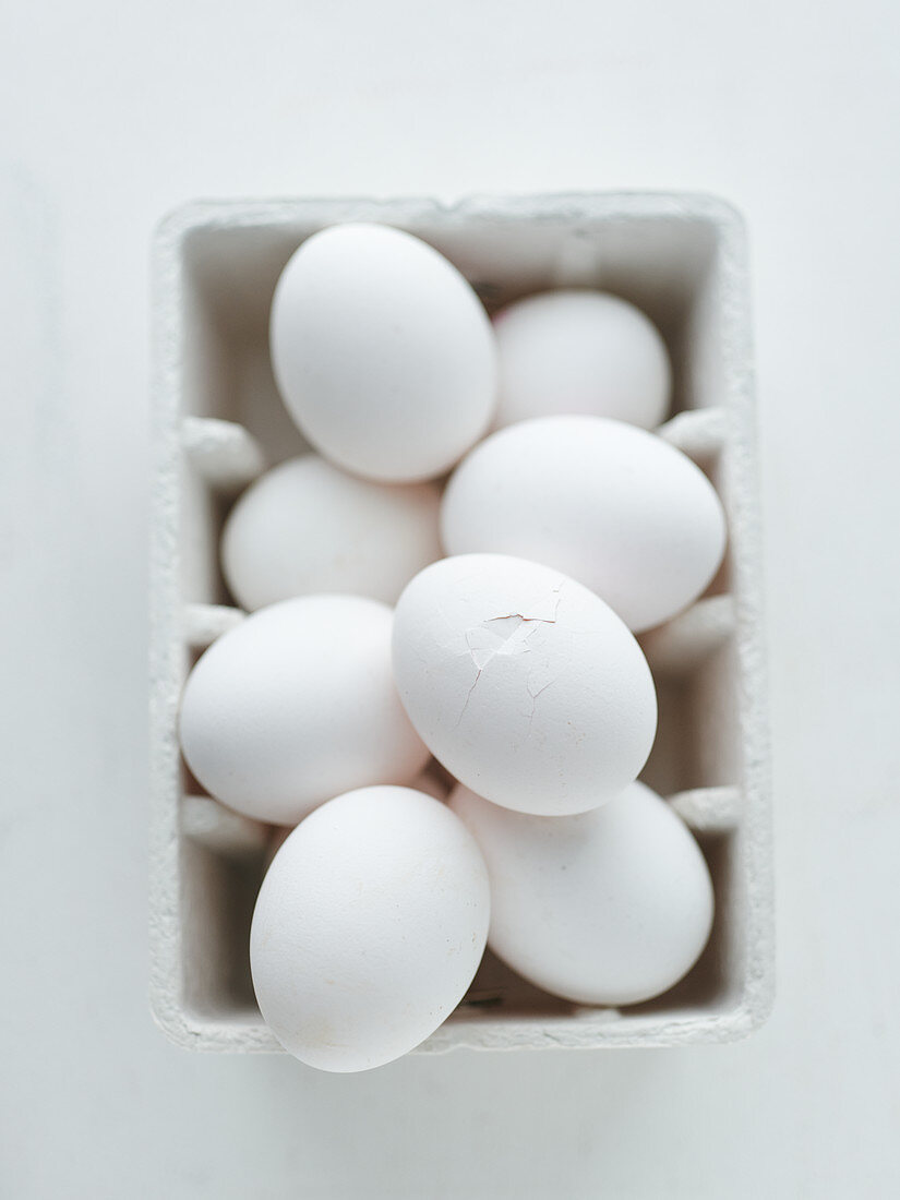 White chicken eggs in a cardboard carton, one with a slightly broken shell