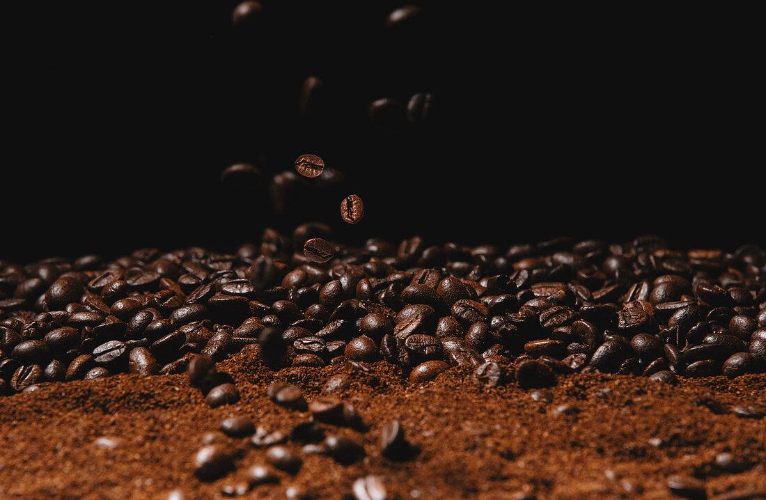 Falling fresh roasted coffee beans and powder coffee