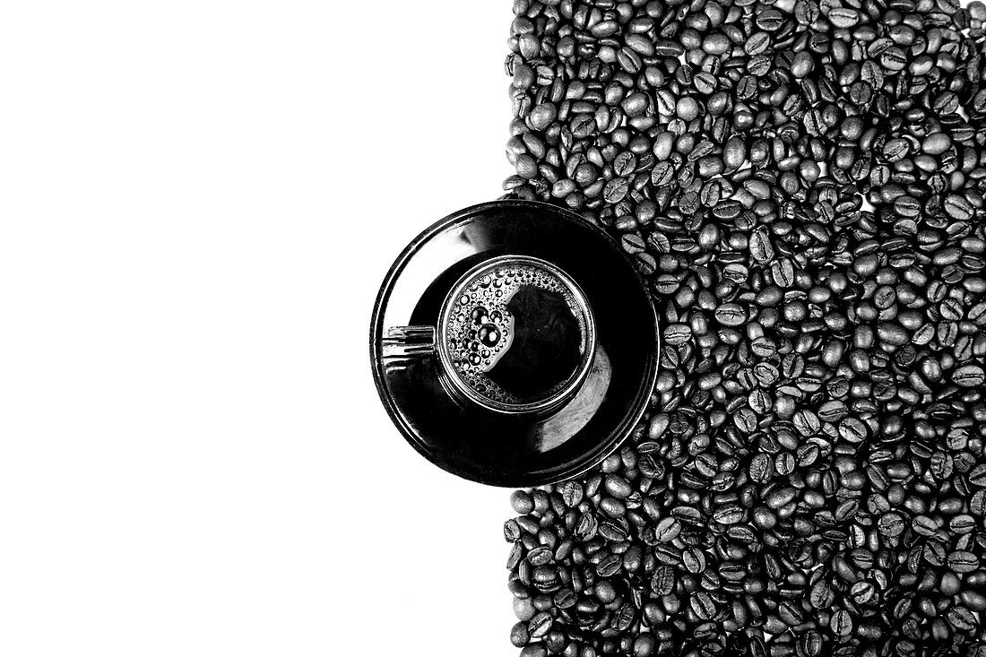 Black cup of coffee on plate with coffee beans