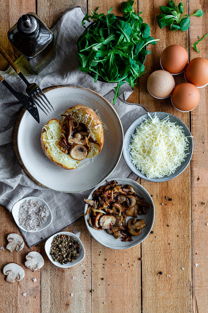 Stuffed potato on wooden table with fried mushrooms, grated cheese and herbs