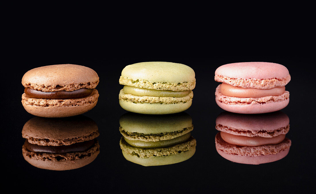 Colorful macaroons stacked displayed on black background