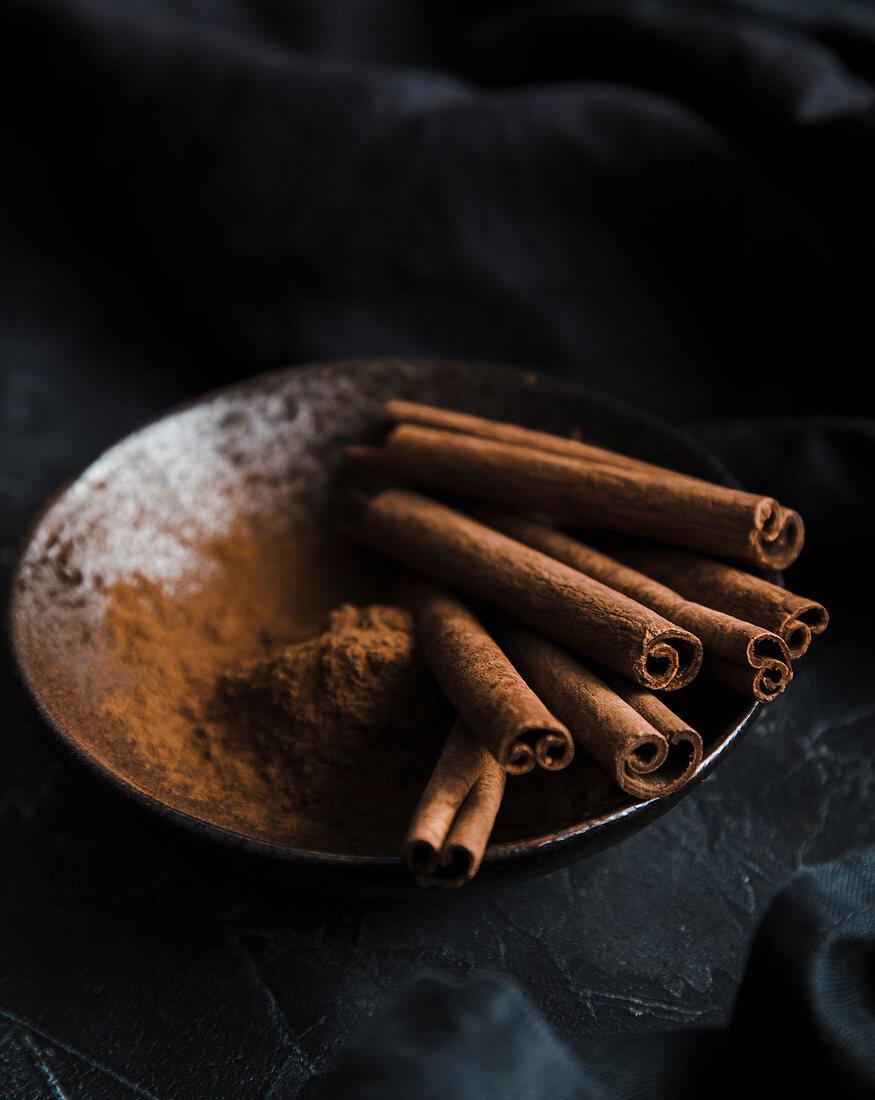 Cinnamon sticks and powder in a bowl, on a dark background