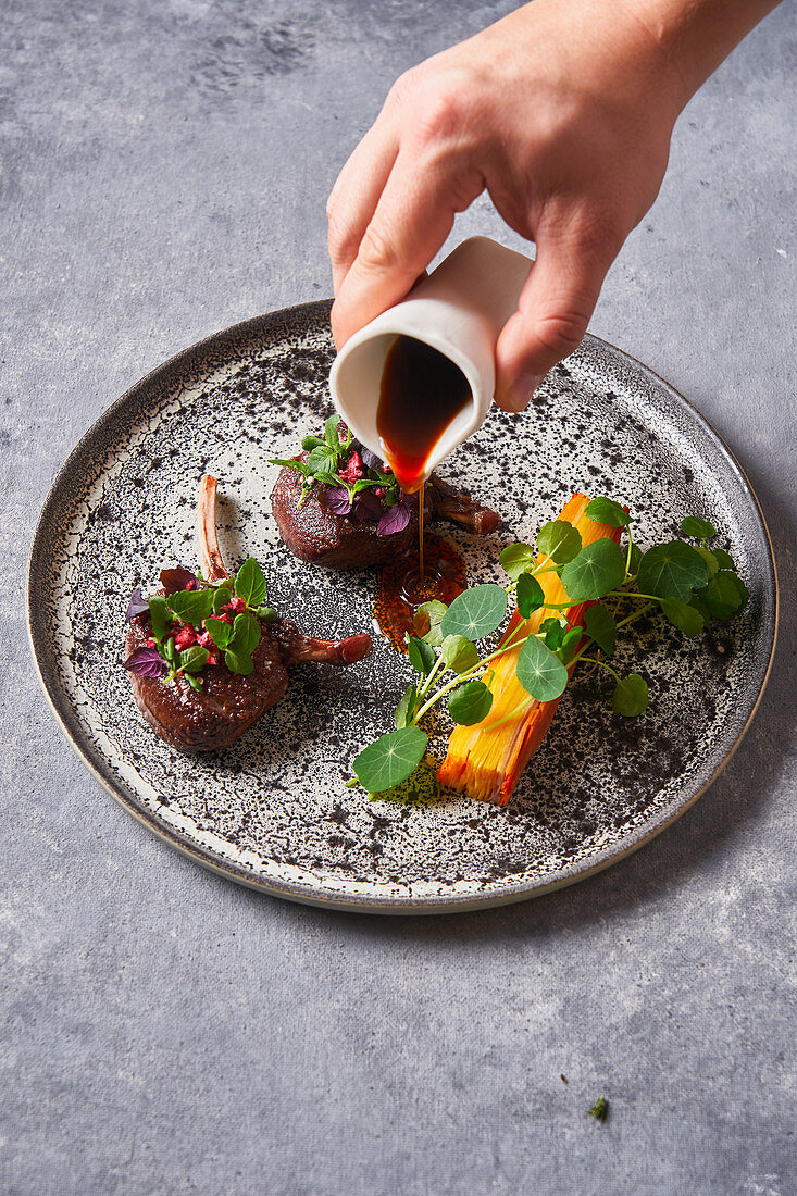 Person adding sauce to meat medallions with herbs on plate on gray stucco table