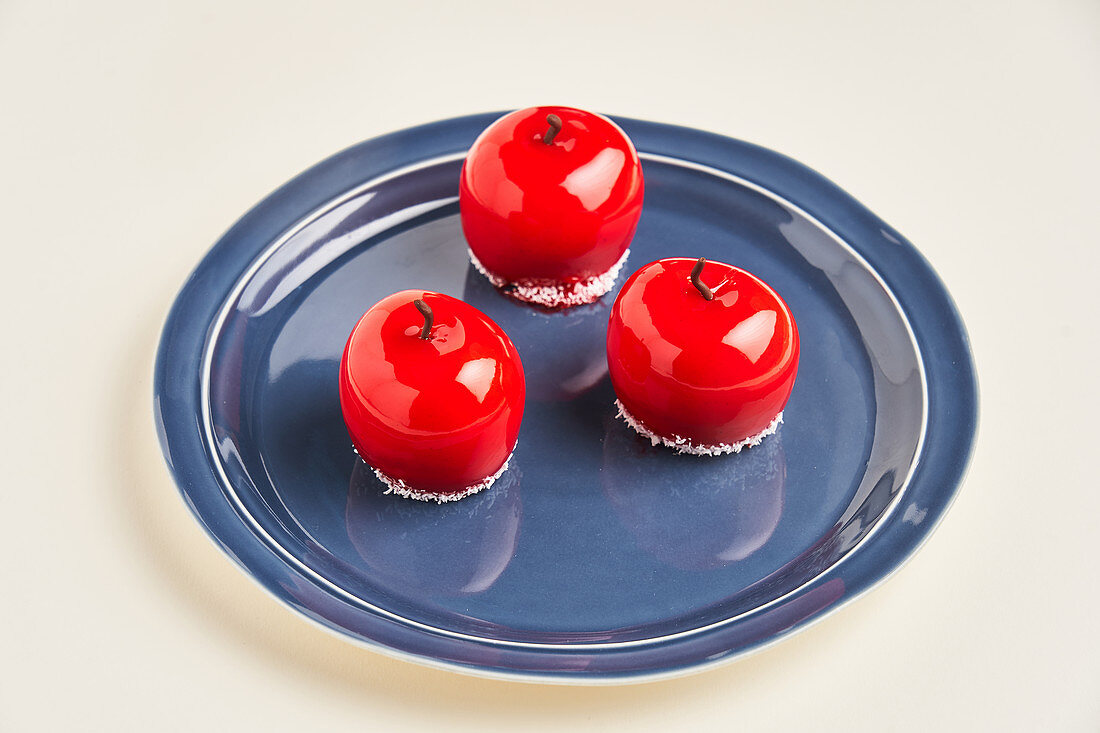 Apple shaped pastry with red icing placed on plate