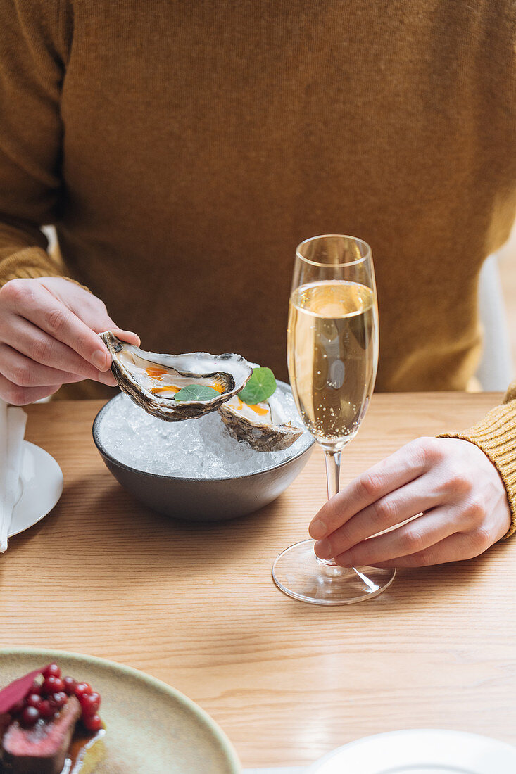 Person with glasses of champagne trying oysters with lemon and herbs in restaurant