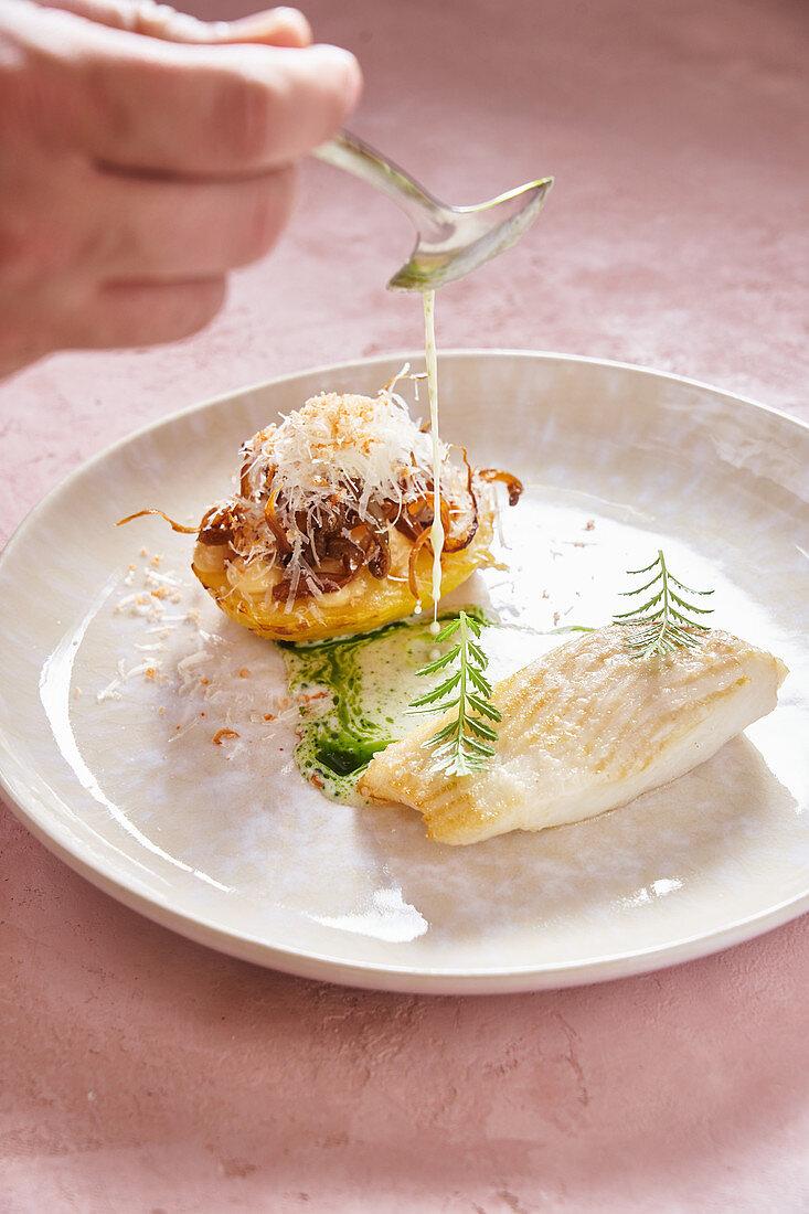 Koch mit Löffel beim Beträufeln eines Fischfilets
