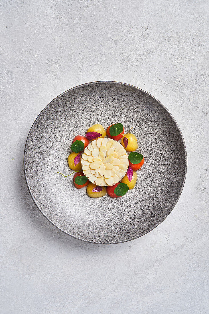 Fish tartare served with almonds and fresh cherry tomatoes