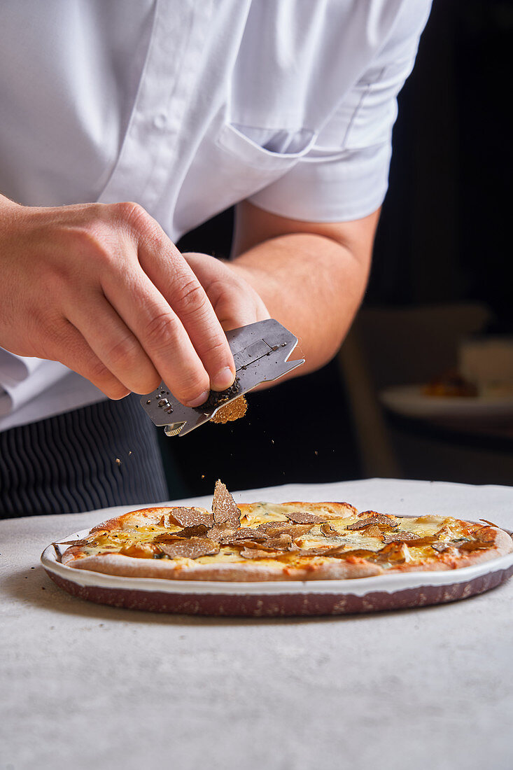Eine Pizza mit frischen Trüffelscheiben bedecken
