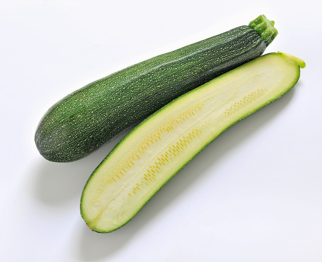 Zucchini, whole and halved on a white background