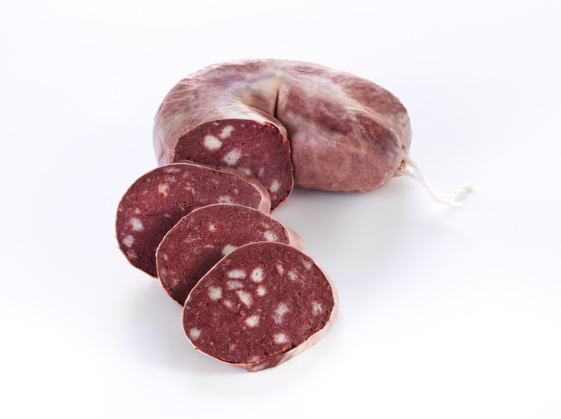 Black pudding in one piece and sliced against a white background