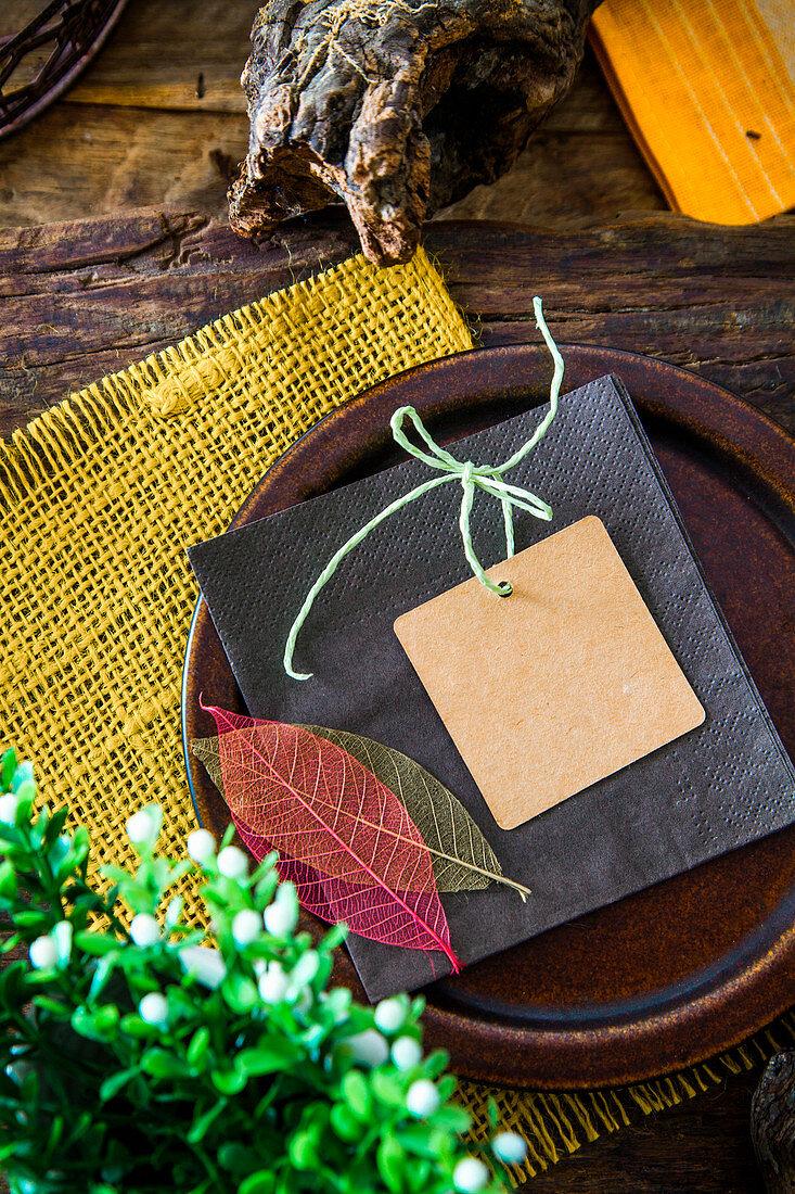 Gedeck mit Kärtchen und Blätterdeko auf rustikalem Holztisch