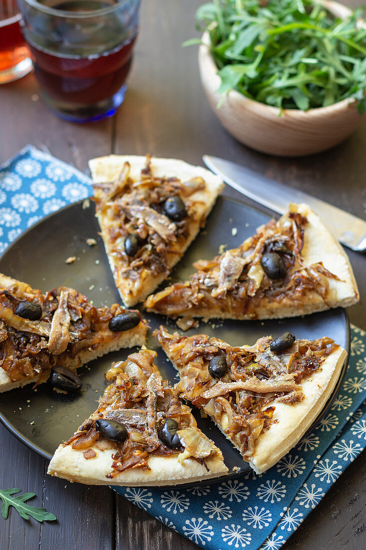 Pissaladière with anchovies, black olives and onions, rocket