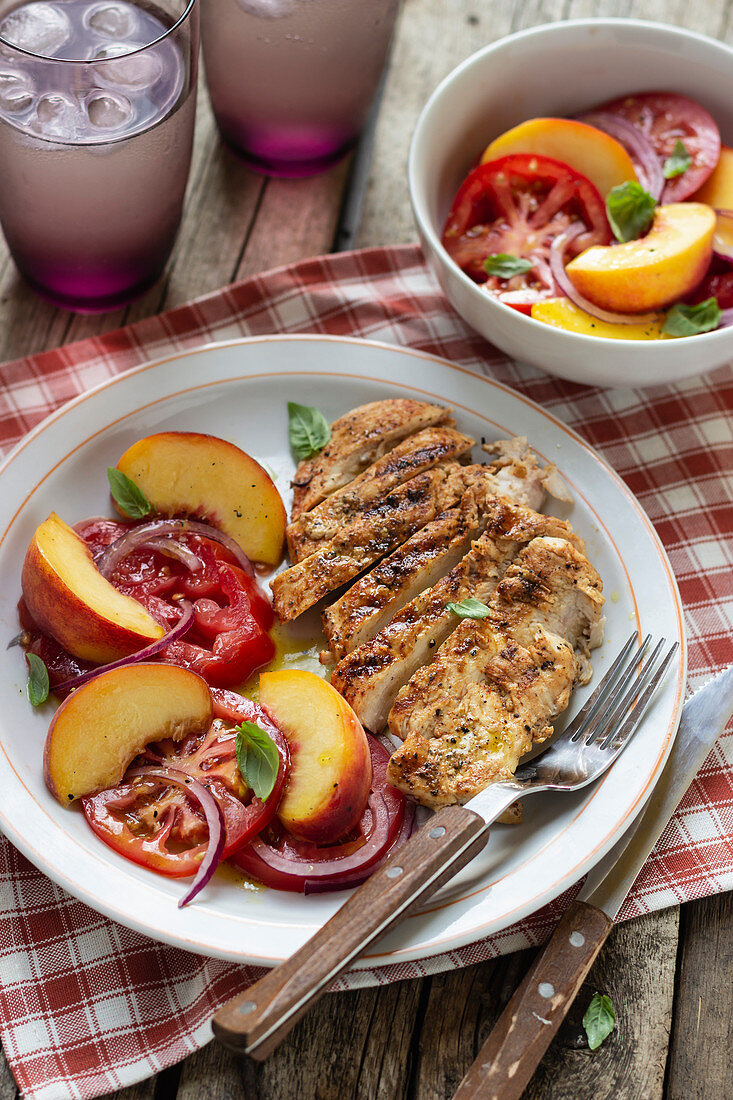 Grilled chicken breast with salad made of tomatoes, peaches, with red onion and basil