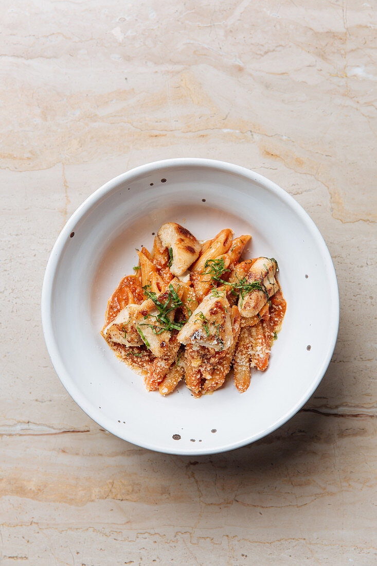 Pasta served with cheese pieces of roasted meat and herbs
