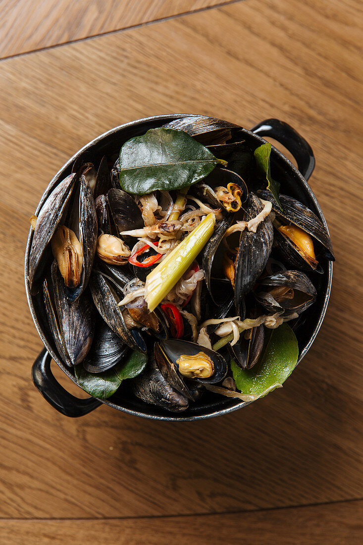 Black mollusk dish with assorted steamed vegetables in black pot on table